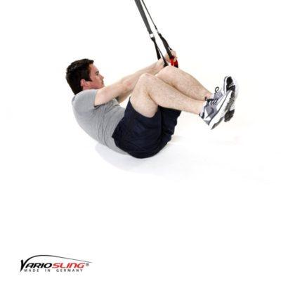 Sling-Trainer Bauchübung – Assisted Crunch, Arme zur Seite mit angehobenen Beinen